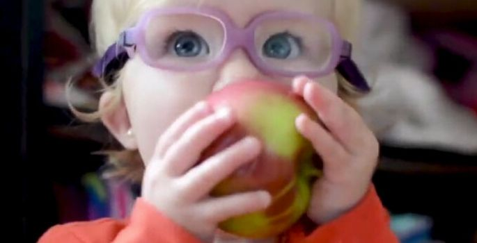 Little girl with glasses eating an apple