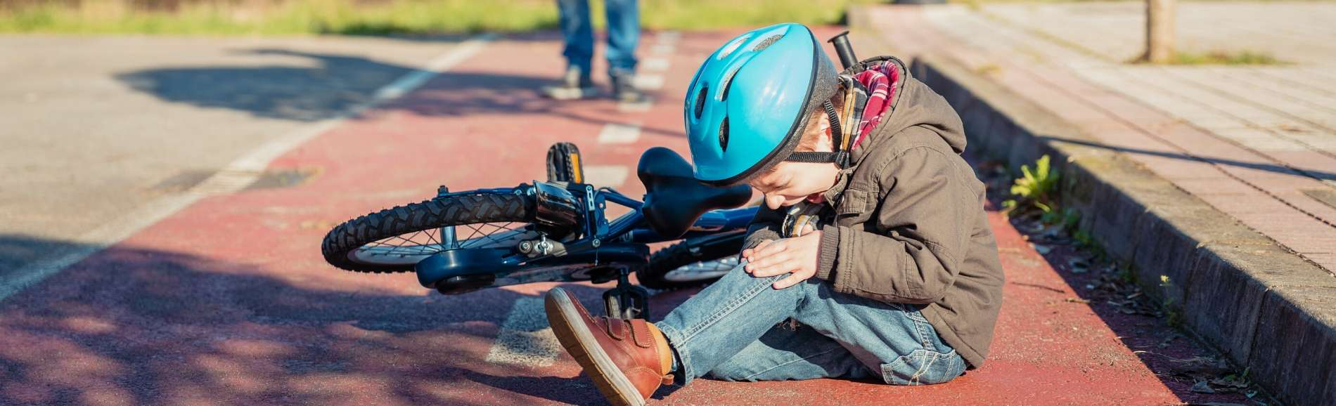 Young boy wearing helmet who's fallen off his bike