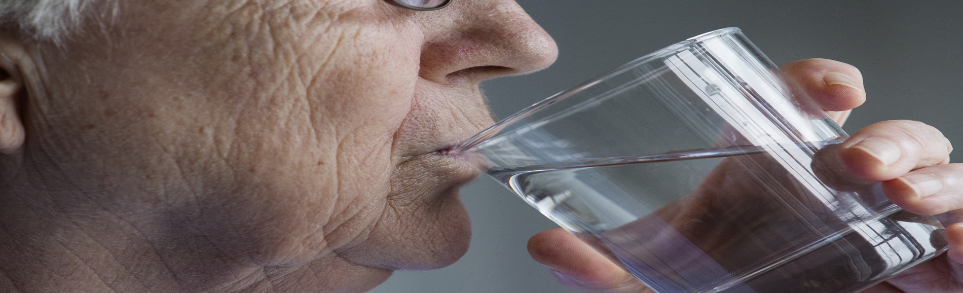Older adult drinking a glass of water